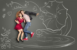 Dancing on vinyl. Happy valentines love story concept of a romantic couple sharing headphones, listening to the music and dancing on a gramophone, against chalk Royalty Free Stock Photos