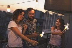 Dancing and waving with sparklers at a rooftop party stock photo