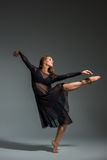 Dancing woman in a black dress. Contemporary modern dance on a gray background. Fitness, stretching model stock photography