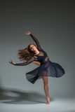 Dancing woman in a black dress. Contemporary modern dance on a gray background. Fitness, stretching model royalty free stock image