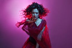 Dancing woman with flying red dress. Beautiful Gothic girl like a witch. Focus on the hand royalty free stock photo