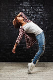 Dancing woman. In jeans and white t-shirt in the dark room Royalty Free Stock Photos
