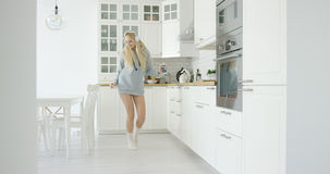 Dancing woman in kitchen Stock Photo