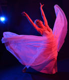 Dancing woman like a butterfly. Blonde young woman is dancing in the dark. Her dress is streaming in the light of the blue and pink photoflashes. She is like a Stock Image