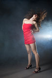 Dancing woman in red dress on black background Stock Images