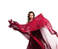 Dancing woman in red dress flying on wind. Dancing woman in red dress waving flying on wind flow with long curly hair Royalty Free Stock Photography