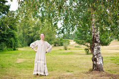 Dancing woman in the Russian national dress. Dancing young woman in the Russian national dress next to a birch in a field Royalty Free Stock Images