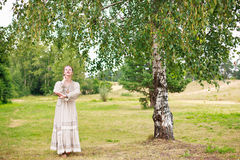 Dancing woman in the Russian national dress. Dancing young woman in the Russian national dress next to a birch in a field Stock Photos