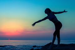 Dancing woman silhouette on the seaside during twilight. Hobby. Stock Photo
