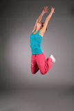 Dancing woman in sportswear in jump with rised han Royalty Free Stock Photos