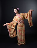 Dancing woman in traditional Japanese kimono on black background Stock Image