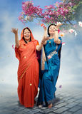 Dancing women in sari under kapok tree branch Royalty Free Stock Photos