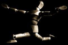 Dancing wooden artist's mannequin. A dancing wooden artist's mannequin in sepia tones royalty free stock images