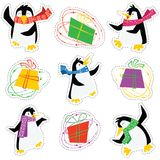 Dancing xmas penguins in a bright scarves and colorful gift boxes. Stickers set. Vector collection of winter holidays animals with presents Royalty Free Stock Photos
