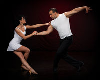 Dancing young couple. Dancing young couple on a dark background Royalty Free Stock Image