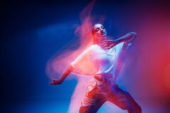 Free Dancing Young Mixed Race Girl Enjoying Moving In Colorful Neon Studio Light. Long Exposure. Ethnic Fiery Dance Royalty Free Stock Images - 225783449