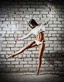 Dancing young woman on wall (dark version) Royalty Free Stock Photography