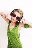 Dancing young woman wearing headphones and sunglasses Stock Photo