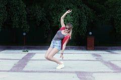 Dancingowa dziewczyna jest ubranym szkła, drelichowi skróty, szara koszula z plecakiem Zdjęcia Stock