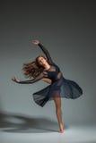 Dancingowa kobieta w czarnej sukni Współczesny nowożytny taniec na szarym tle Obraz Royalty Free