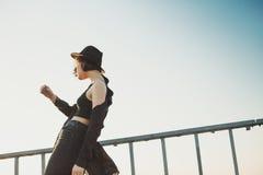 Dancingowa młoda kobieta w czarnym kapeluszu i ubraniach Obraz Stock