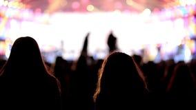 Dancingowej dziewczyny fan sylwetki na koncertowych rozblaskowego światła rozochoconych rękach w powietrzu zdjęcie wideo
