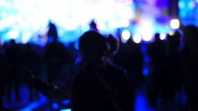 Dancingowej dziewczyny fan sylwetki na koncertowych rozblaskowego światła rozochoconych rękach w powietrzu zbiory wideo