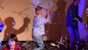 Dancingowi dzieci rzuca w górę świecidełka na szarym tle, zwolnione tempo zbiory