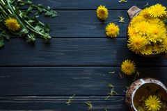 Dandelion flowers on a black wooden table royalty free stock photos
