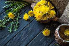 Dandelion flowers on a black wooden table 3 stock photos