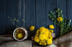 Dandelion flowers on a black wooden table 2. Dandelion flowers and leaves and healthy tea on a black wooden table royalty free stock photography