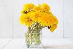Dandelion flowers in glass with water Stock Photography