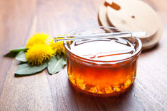 Dandelion honey on rustic wooden table. Honey in glass with fresh dandelion blossoms and leaf on a brown wooden table Royalty Free Stock Images