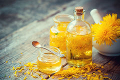 Dandelion tincture or oil bottles, mortar and honey on table. Royalty Free Stock Images