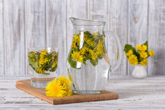 Dandelion tisane tea with fresh yellow blossom inside tea cup, on wooden table Royalty Free Stock Image