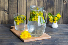Dandelion tisane tea with fresh yellow blossom inside tea cup, on wooden table Stock Photo