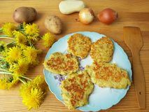 Dandelions flowers with potatoes and onion burgers Royalty Free Stock Photography