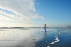 Happy woman walking on the beautiful beach. Royalty Free Stock Photography