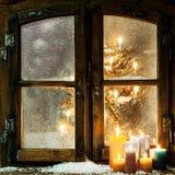 Dando boas-vindas à janela do Natal em uma cabana rústica de madeira Fotografia de Stock