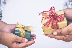 Dando a caixa de presente dentro com mãos em dias especiais para o perso especial fotos de stock royalty free