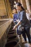 Dando a esmola na estátua da Buda do sono em Wat Pho Temple imagens de stock royalty free