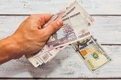 Dando i lotti di soldi russi per lo scambio a cento bambole degli Stati Uniti Immagine Stock Libera da Diritti