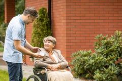 Dando o copo do chá à mulher superior deficiente de sorriso na cadeira de rodas fotografia de stock