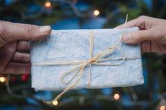 Dando a um Natal o presente azul na frente da luz de Natal Foto de Stock
