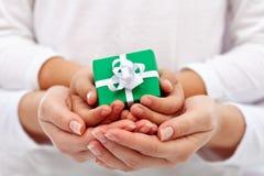 Dando un presente - mani della donna e del bambino con il contenitore di regalo Fotografie Stock Libere da Diritti