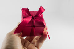 Dando un regalo, regalo rojo hermoso presente en un fondo blanco Imagen de archivo libre de regalías