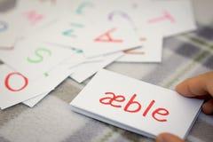 Danese; Apprendimento della parola nuova con le carte di alfabeto; Scrittura del A Fotografie Stock Libere da Diritti