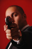 Danger!. Man pointing a gun straight at the camera. Focus is on the gun Stock Image