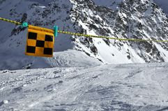 Danger. Avalanche danger flag intending to barr the way for safety reasons, but skiers have ignored it stock image