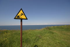 Danger abyss. Danger sign at a limestone cliff, in Paldiski, Estonia Royalty Free Stock Photos